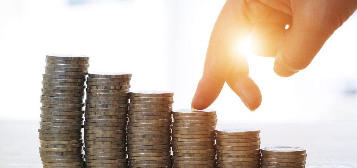 dois dedos de uma mão subindo moedas empilhadas como uma escada com luz de fundo (como um por do sol).